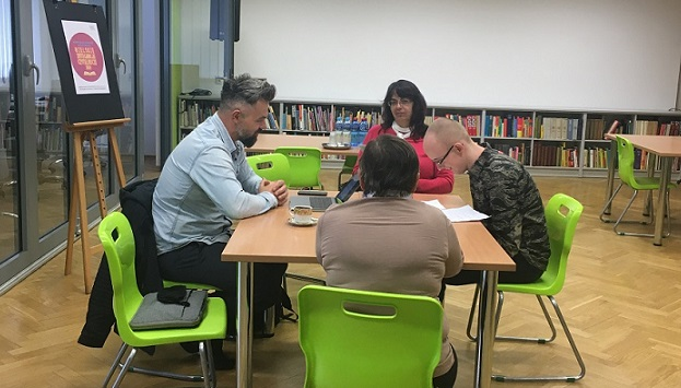 Przy dużym stole siedzą dwie kobiety i dwóch mężczyzn, jeden z nich pochyla się znacząco nad tekstem, czyta. Drugi patrzy w niego.