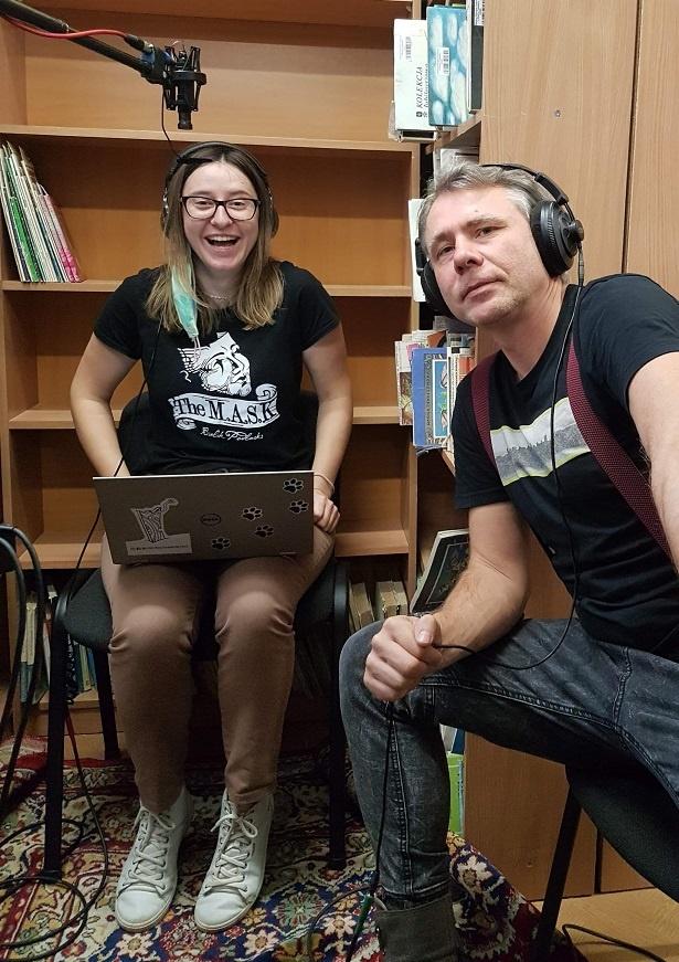 Dwie postaci: po lewej roześmiana dziewczyna w okularach i w dużych słuchawkach, nad nią widoczny mikrofon; po prawej mężczyzna opiera się o swoje kolano, ściskając kabel słuchawek, które ma na głowie. obydwoje patrzą prosto w obiektyw